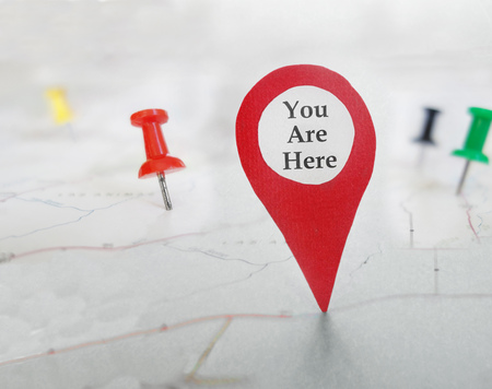 You Are Here locator symbol on a map with tacks