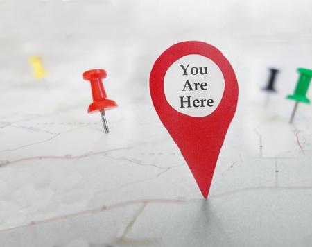 Usted está aquí símbolo del localizador en un mapa con tachuelas Foto de archivo - 80326812