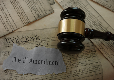 First Amendment news headline on a copy of the US Constitution with gavel