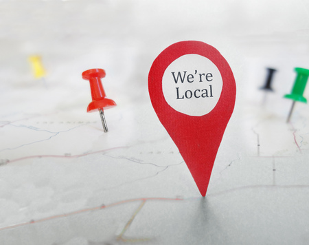 Red locator symbol with We're Local message, on a map with tacks Stock Photo