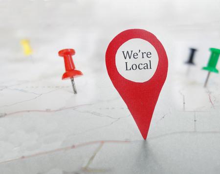 Rood locatorsymbool met We're Local-bericht, op een kaart met kopspijkers Stockfoto