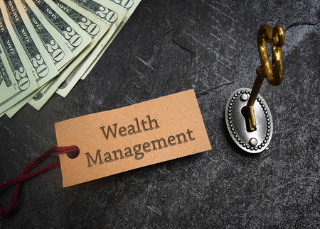 Wealth Management tag and gold key with cash