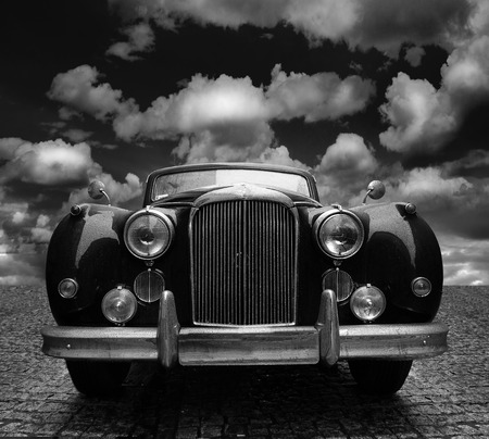 Classic car on cobblestone street, with rain drops and dramatic sky