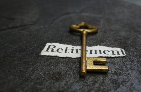 Closeup of a gold key on paper Retirement message