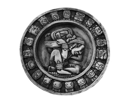 A carved stone circular Mayan calendar isolated on white