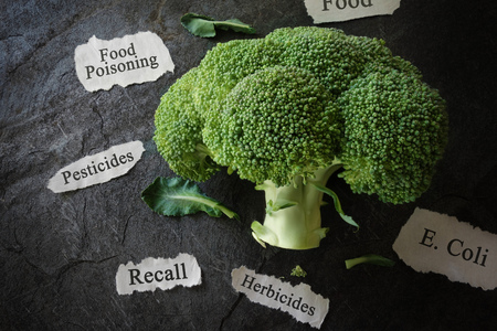 Broccoli with various food safety related news headlines Stock Photo
