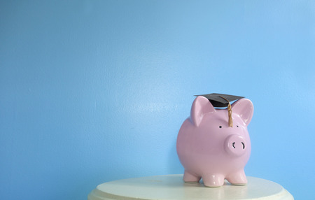 Piggy bank wearing a graduation cap, on blue background with copy space