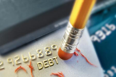 Pencil erasing credit card debt Foto de archivo