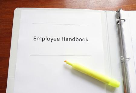 蛍光ペンで机の上の従業員ハンドブック