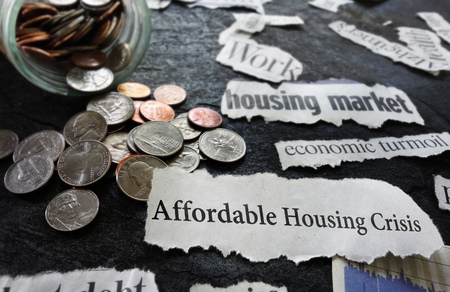 Affordable Housing Crisis newspaper headline and related economic news, with coins Stok Fotoğraf - 91390596