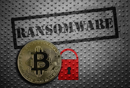 Ransomware stamped on metal with red lock and a bitcoin