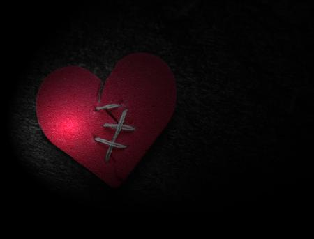 Broken red heart with threaded stitches on dark background