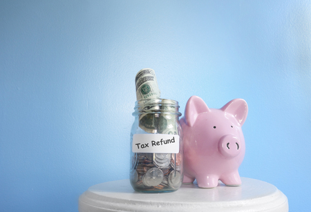 Piggy ban with Tax Refund label on a coin jar