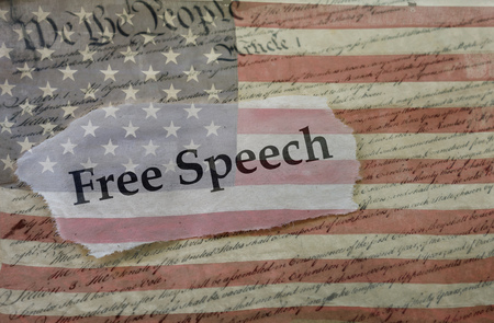 Free Speech news headline on a copy of the  United States Constitution and the US flag Banco de Imagens