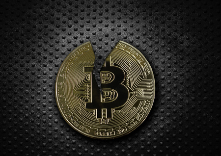 Cracked gold bitcoin on grunge rivet metal background Stock Photo