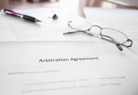 An Arbitration Agreement document on a desk with glasses and pen Foto de archivo
