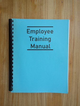 Blue employee training manual on a desk