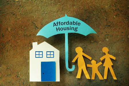 Paper cutout family with house under an Affordable Housing umbrella