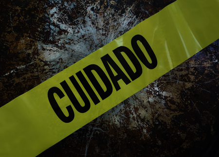Yellow Cuidado (Caution) tape over textured background