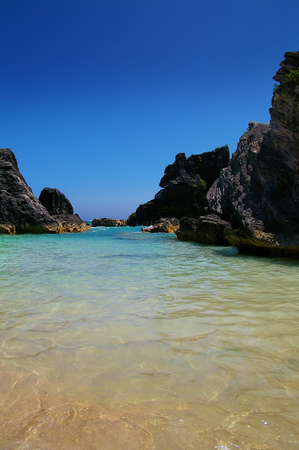 Sandy secluded cove surround by rocky coast in Bermuda