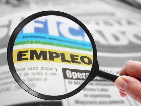 Person using a magnifying glass to look at a Spanish language newspaper classified employment ( empleo )