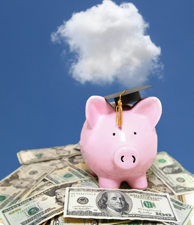 piggy bank with graduation cap, on cash with blue sky Stock Photo