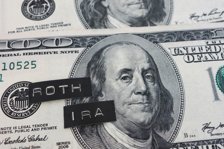 Roth IRA labels on hundred dollar bills                              Stock Photo