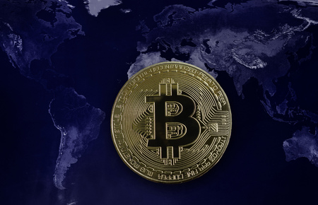 Gold Bitcoin over a world map