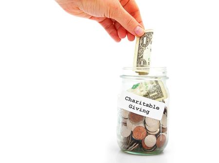 Mano poniendo un dólar en el tarro de donaciones caritativas, aislado en blanco