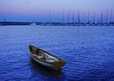 Small sailboat at the marina at dusk in Bayfield Wisconsin with the Apostle Islands in the distance Stock Photo