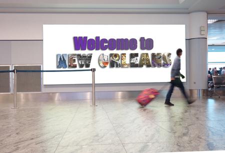 """Ein Mann mit Koffer geht in einen Flughafen, hinter ihm das Schild """"Welcome to New Orleans"""" Standard-Bild"""