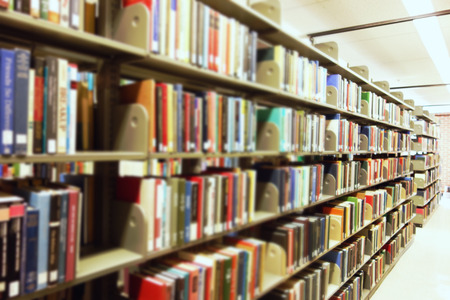 Books on library shelves with blurred titles