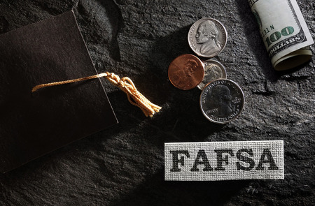 FAFSA (Free Application for Federal Student Aid) text with graduation cap and money -- financial aid concept Imagens