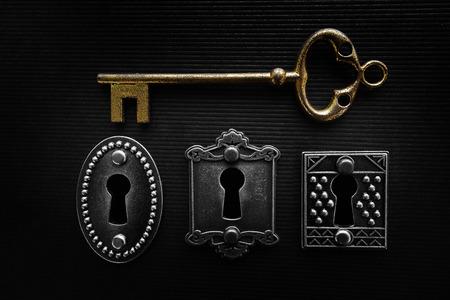 Three vintage locks and gold key on dark background Stok Fotoğraf