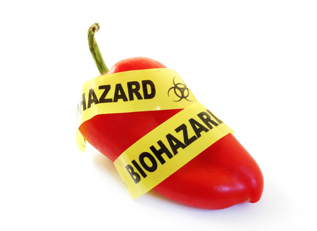 Red pepper with bio-hazard tape.food safety concept