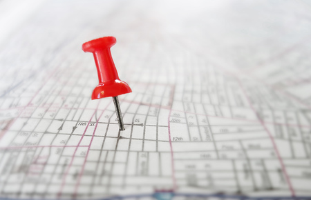 Closeup of a red push pin tack in a street map Stock Photo