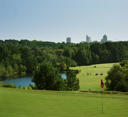 Golfers on a course in Raleigh NC with the green in the foreground and city skyline in the distance Imagens