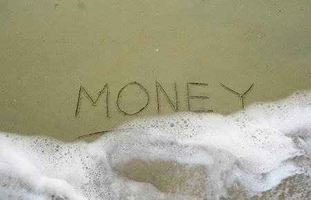 An ocean wave washing away Money written in the beach sand                                Foto de archivo