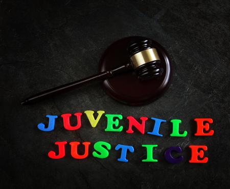 Justicia de menores escrito en letras coloridas, con martillo legal Foto de archivo