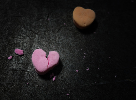 Pink candy heart broken in two on dark textured background Stock Photo - 120352834