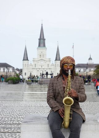 NEW ORLEANS,LAUSA -03-17-2019: A musician plays jazz on the saxophone in front of St Louis Cathedral in New Orleans French Quarter 에디토리얼