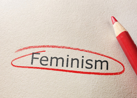 Feminism text circled in red pencil on textured paper Reklamní fotografie - 122273064