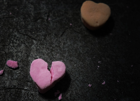 Cracked pink candy heart on dark background Stock Photo - 122273068