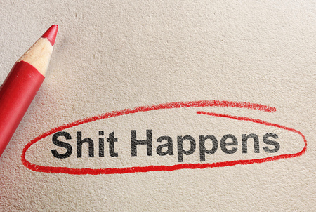 Shit Happens text circled in red pencil on textured paper