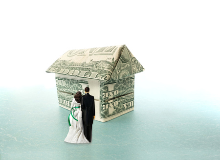 Young married couple figures looking at a dollar house -- home buying concept