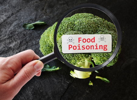 Food Poisoning label on broccoli examined by a person with magnifying glass
