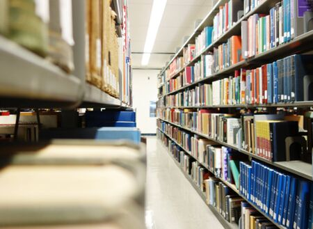 Books on shelves in a college library Banco de Imagens