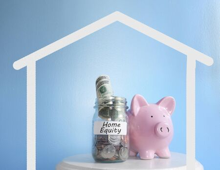 Piggy bank and coin jar with Home Equity savings coin jar Stock Photo