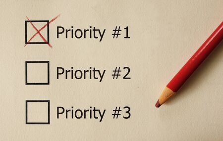 Priority1 check box with red pencil on paper