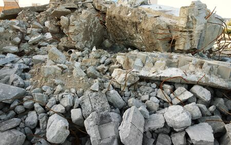 A pile of concrete rubble and rebar from a demolished building